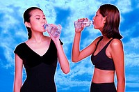 Two women in fitness wear drinking bottled water.