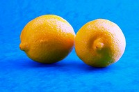 Two lemons against a blue background.