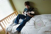 Boy playing guitar and listening to ipod.