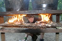A boy scout checks on the fires he built for heating dish water during summer camp in Missouri. USA