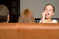 Girl eating popcorn with family