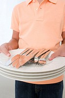 Boy holding plates and cutlery