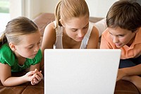 Brother and sisters using laptop