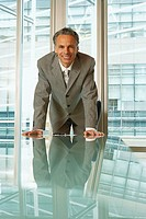 Smiling businessman in modern office (thumbnail)