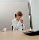 Woman sitting in an office and blowing her nose