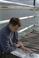 Man sitting on a landing stage while reading a newspaper, selective focus