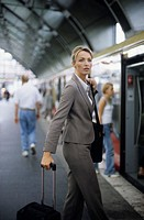 Businesswoman with Handbag and Suitcase standing on a Departure Platform - Train - Travel