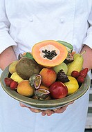 Chef holding bowl of exotic fruits