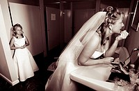 Bride preparing in bathroom with flower girl