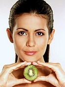 Woman holding half a kiwi fruit