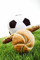 Sausage in a roll in front of a football