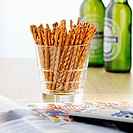 Salted sticks in glass, beer bottles in background