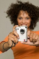 Woman with frizzy hair using camera, indoors