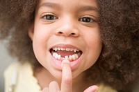 Girl (4-6) pointing at tooth, close-up