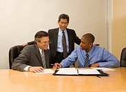 Three businessmen looking at documents in conference room, smiling