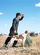 Businessman standing with English Pointer dog in desert