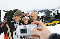 Person taking photograph of three friends smiling with skis