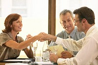 Businessman and woman shaking hands over restaurant table
