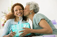 Mother kissing adult daughter, holding present