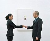 Man and woman standing by picture exchanging business card