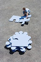 Young man fitting large blue jigsaw pieces together, elevated view