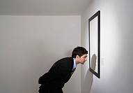 Businessman looking at picture on wall, side view