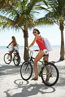 Two young women on bicycles on beach, portrait