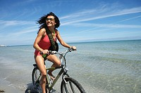 Young woman riding bicycle on beach, smiling, close-up