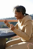 Senior woman doing jigsaw puzzle in terrace, side view, close-up