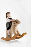 Toddler girl (21-24months) smiling on rocking horse, portrait