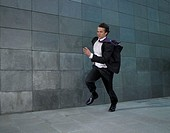 Businessman running against wind