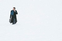 Businessman using mobile phone walking through snow