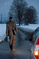 Businessman walking in snow on country road, car in foreground, dusk