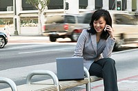 Woman sitting on bench using mobile phone with laptop