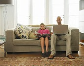 Girl (7-9) reading on sofa next to father using laptop