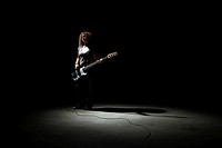 Teenage girl (13-15) playing bass guitar