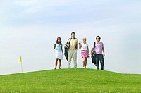 Two couples standing on hill on golf course