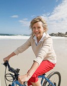 Mature woman riding bicycle on beach, smiling, portrait