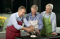 Three mature men in kitchen, one cracking egg over bowl, smiling