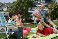 Grandparents having picnic on lawn with grandchildren (2-5)