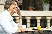 Senior woman sitting at outdoor cafe using mobile phone, smiling
