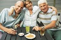 Senior woman sitting with arms around senior and mature man, smiling