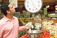 Mid adult man weighing vegetables in a supermarket
