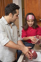 Young man washing dishes with a girl sitting beside him