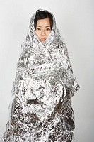 Woman with silver survival blanket, portrait