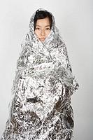 Woman with silver survival blanket, portrait