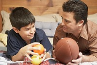 Father and his son lying on the bed holding fruit and a football