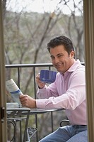 Portrait of a mid adult man holding a newspaper and a cup of coffee