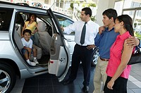 Car salesman showing car to family in showroom, children inside SUV