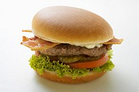 Hamburger with bacon, mayonnaise, gherkins, tomato, lettuce